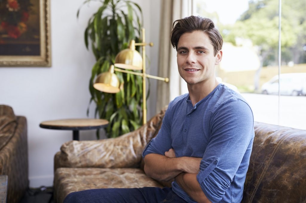Young male business owner sitting on sofa in a coffee shop