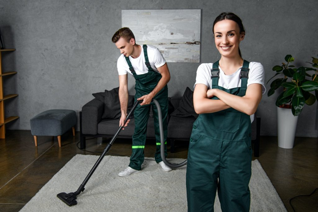 young male cleaner using vacuum cleaner and female coworker standing with crossed arms and smiling
